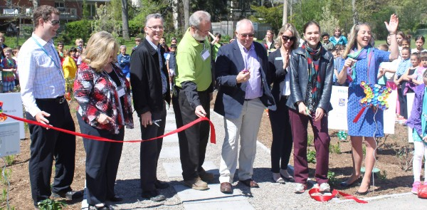 People cutting a ribbon to mark the new rain garden