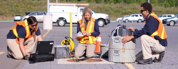 Three technicians downloading water quality data from a manhole