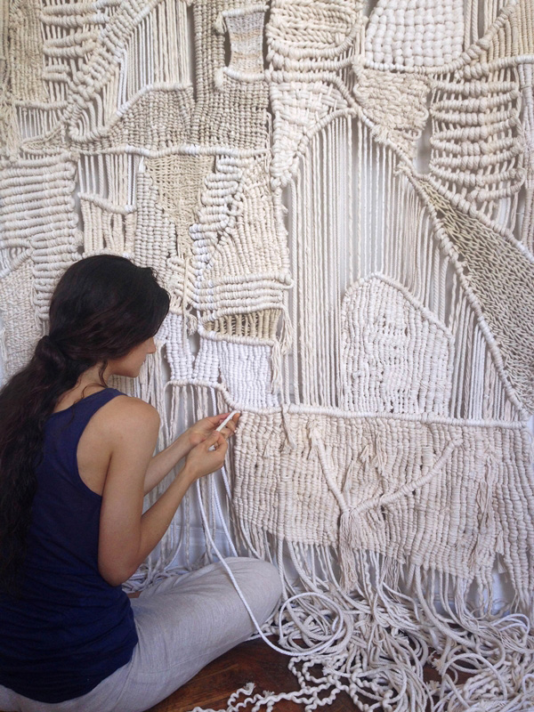 Artist seated working on macrame wall hanging