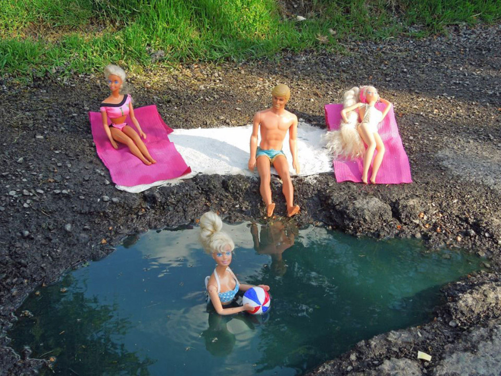 Barbie dolls decorate a pothole, from the guerrilla art campaign Pothole: Positively Filling Negative