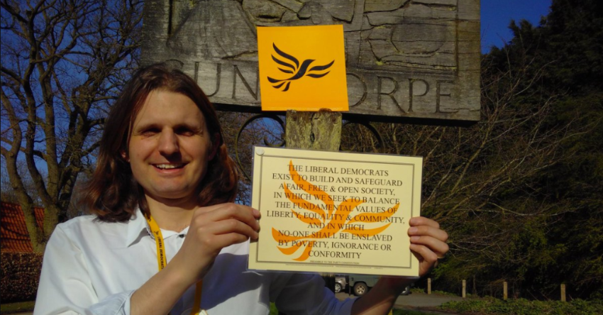 Steffan Aquarone holding up the preamble to the Liberal Democrat constitution