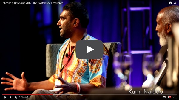 A screen grab from a video about the 2017 Othering and Belonging Conference shows Kumi Naidoo speaking on a panel