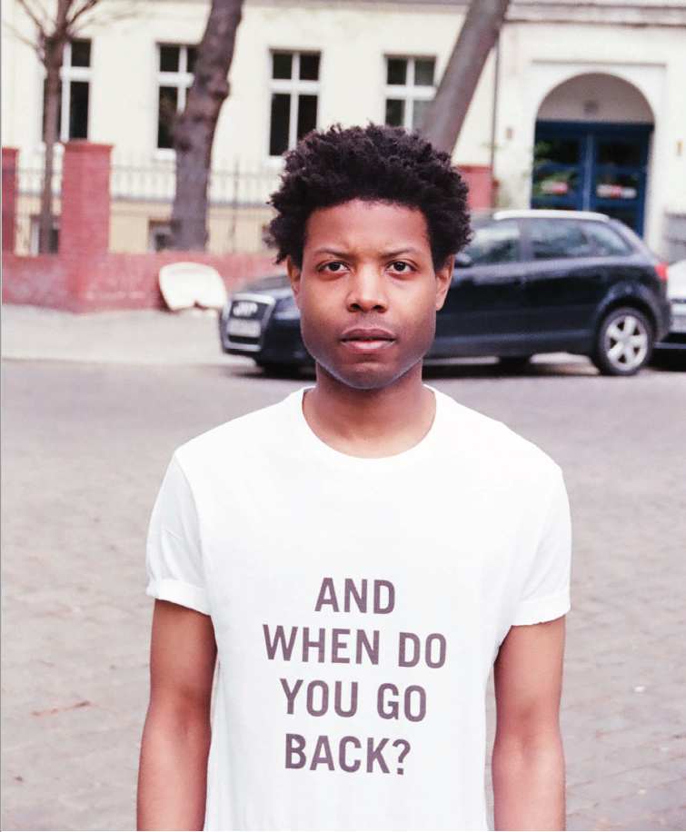 """Image detail of Isaiah Lopaz photo Him Noir showing a Black man looking at camera wearing tsihirt that says """"And when do you go back?"""""""