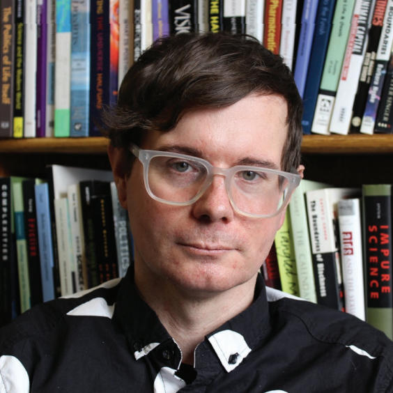 Headshot of Eric Stanley in front of books