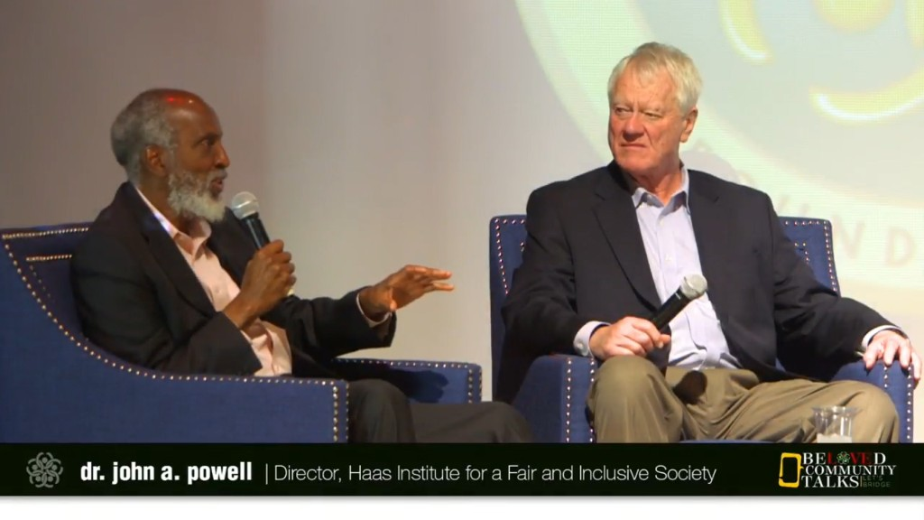 john powell with microphone, seated on stage, next to another speaker