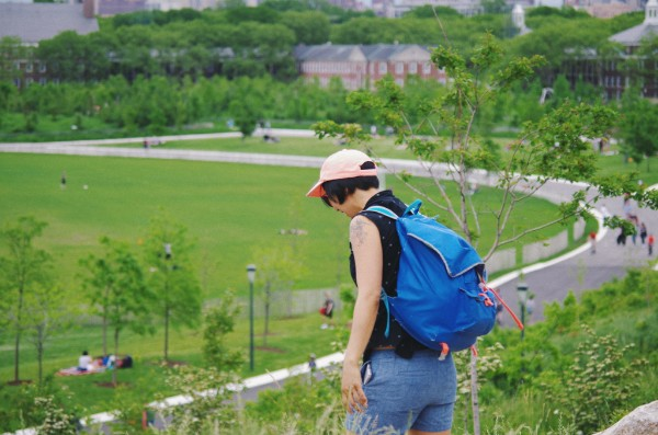 Photo of artist Christine Wong Yap standing with her back to the camera at an elevation overlooking a large, green grassy area with some trees and brown buildings further in the background in what appears to be a university campus.