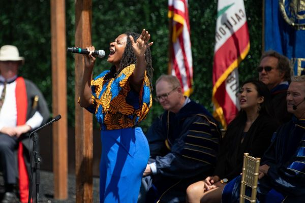 Image of Takiyah Franklin singing into a microphone with eyes closed and  head back on a stage with four people seated behind her