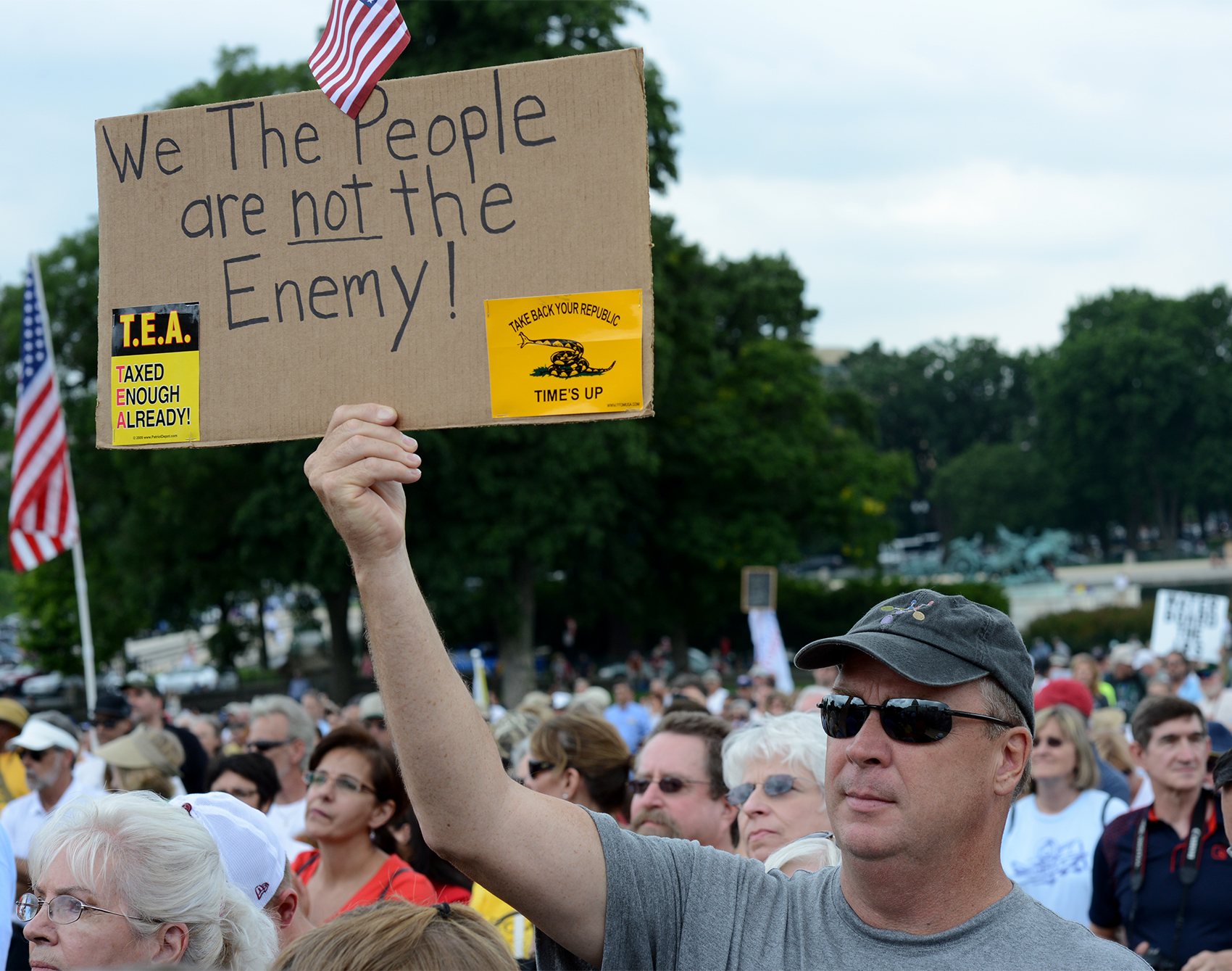 """A male Tea party supporter holding up a sign that says """"We the people are not the enemy"""" at a Tea Party IRS Rally. Photo by Stephen Melkisethian"""