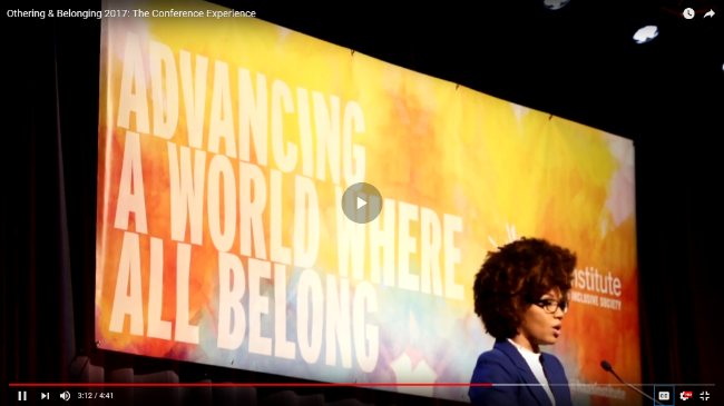 """Image of speaker LaToya Ruby Frazier at a microphone with a banner behind her on the stage that reads """"Advancing a World Where All Belong"""""""