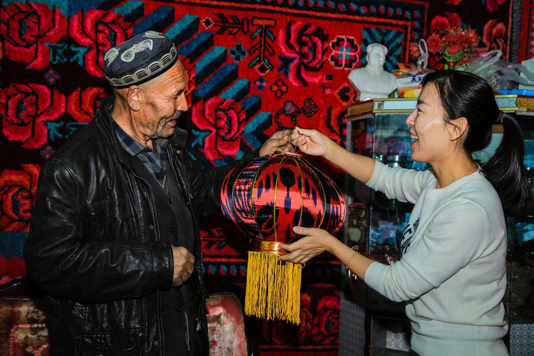 2017年11月11日,新疆呼圖壁縣園戶村鎮上三工村,該縣縣委宣傳部幹部許文玲給結對親戚艾則孜·賽麥提(左一)送去艾德萊斯燈籠。
