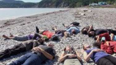 Photo of a number of people are lying on their backs in a circle on the beach in Gaspé, Québec.