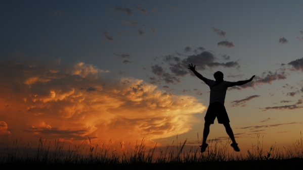 A silhouette of a person jumping against a sunset lit cloud over the prairies