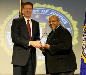 FBI Director James Comey presents Wilson with Award