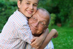 Grandfather being hugged by grandson