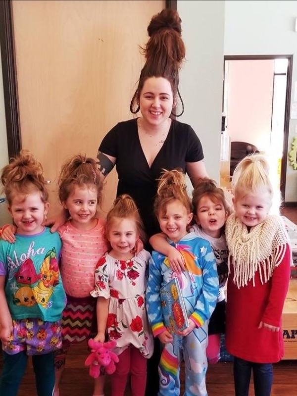 Smiling teacher and children from Toddles Preschool with fun Dr. Seuss hair.