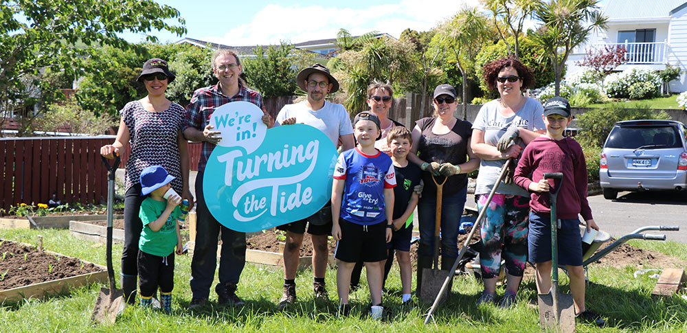 Garden Blitz gardeners holding the Turning the Tide sign.