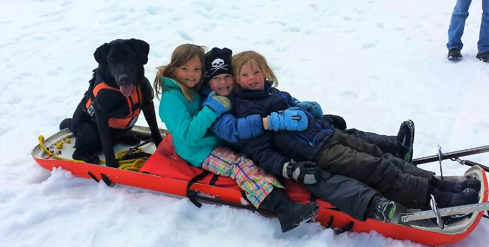 Winter Adventurers ride the rescue toboggan with Odin, the avy dog from CAIC
