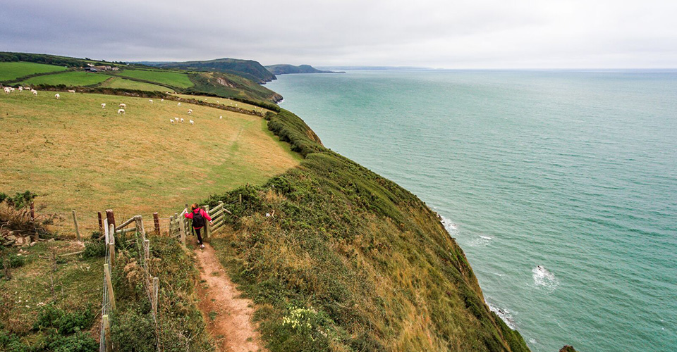 A person walking along a path beside a cliff