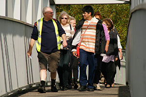 A man wearing a high-vis top, walking and talking with walkers as they cross a bridge