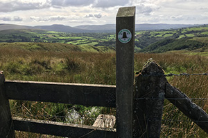 A waymarking of the Cambrian way in front of a valley view