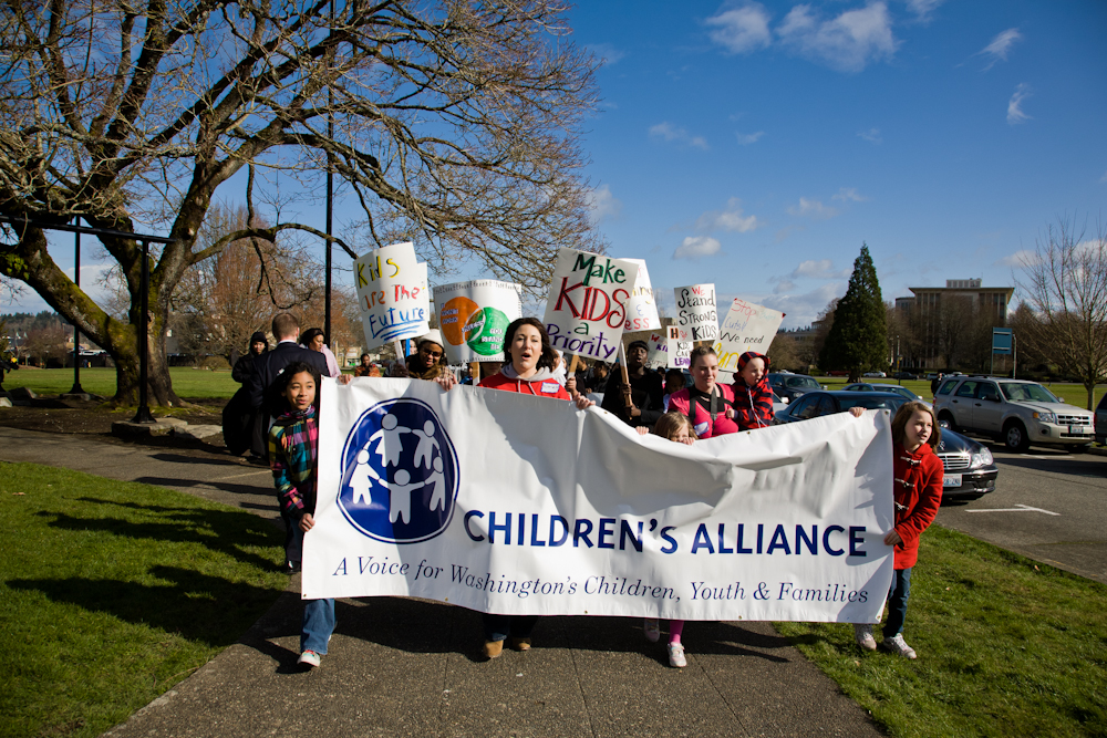 Kids and adults marching with Children's Alliance banner