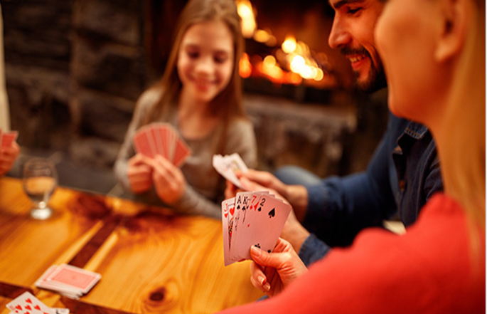 Friends or family take a break from their digital devices to play a game of cards.