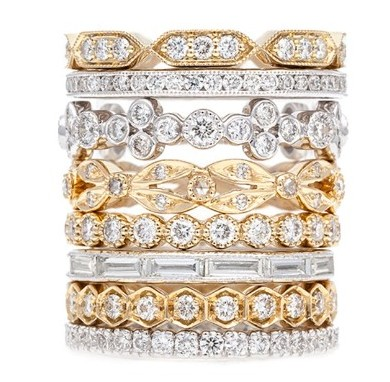 Stack of white and yellow gold diamond wedding bands on a white background.