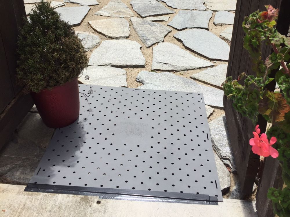 A Beach Trax panel over rock pavers in a driveway secured to the cement using black tape.