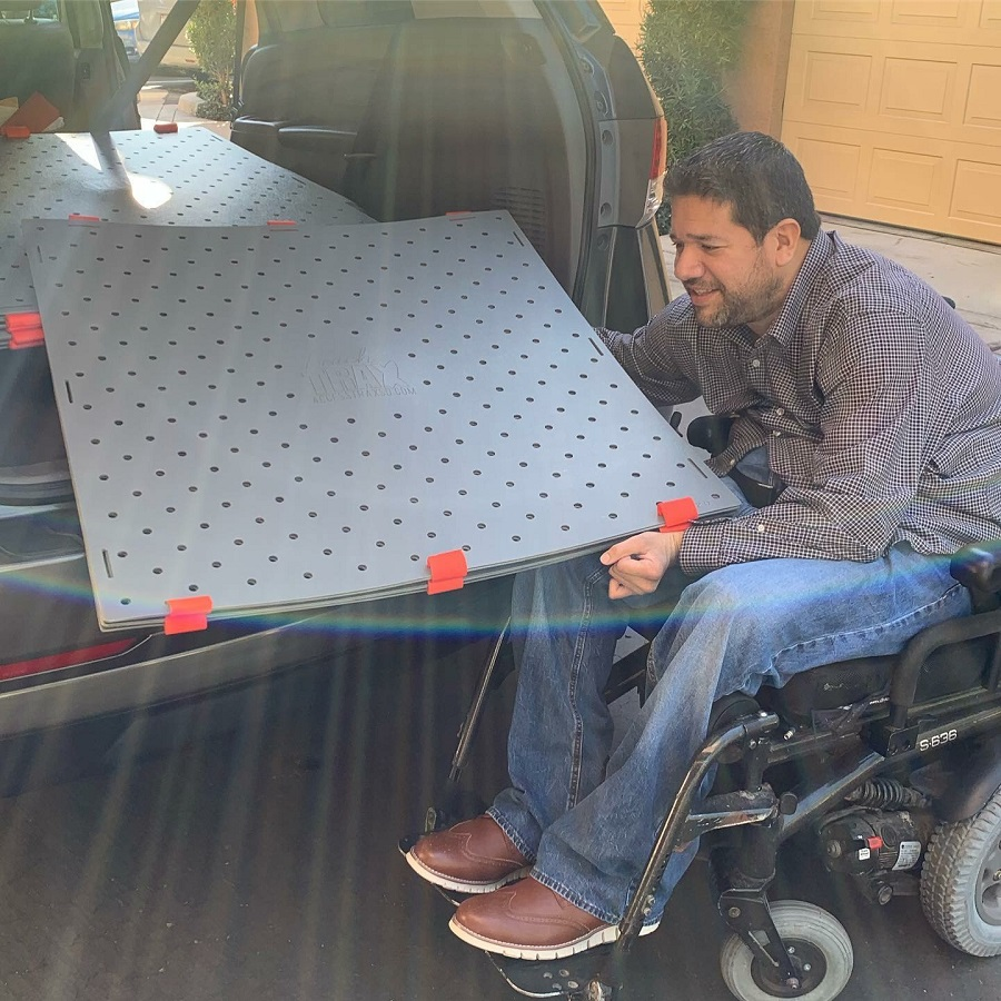 A man using a power wheelchair holds a stack of grey Beach Trax panels as they slide into the trunk of his car.