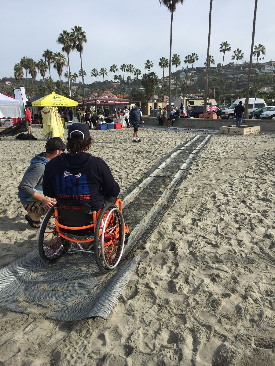 Eric Packard and adaptive surfer Christiaan Bailey talk about the chicken mesh & wire pathway stretching down the beach.