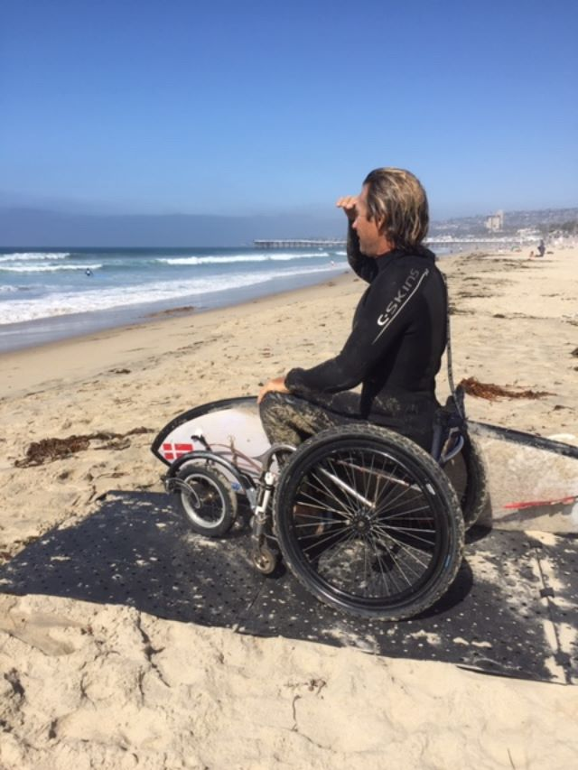 Adaptive surfer Bruno Hansen looks at the waves while using the black Beach Trax pathway at the beach with his surf board next to him.