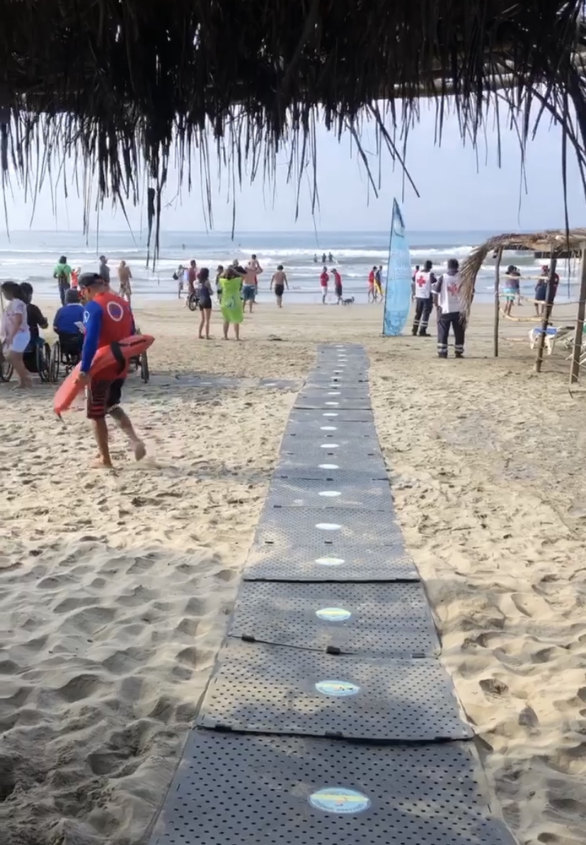 A Beach Trax pathway leading to the ocean from under a palapa cabana at a beach event.
