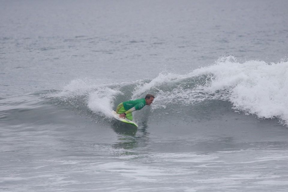 A surfer wearing a green rash guard kneeling on the surf board leans in to catch a wave.
