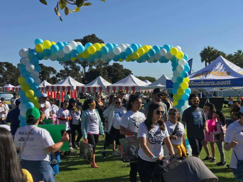 "A diverse crowd of people wearing white ""Walk & Roll"" tshirts walks through the balloon-framed start line at the event."