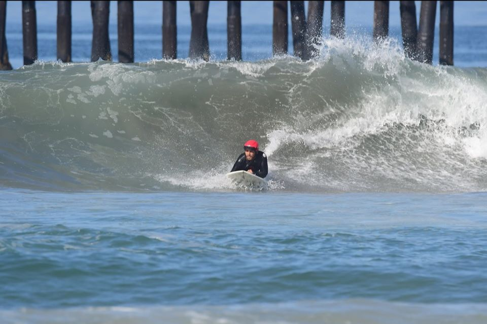 A surfer wearing a red helmet and blackwetsuit catching a wave while prone (lying down) on the surf board.