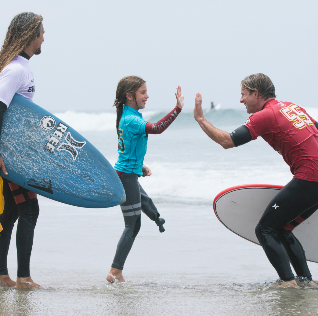 A male surfer and young female adaptive surfer are about to high-five in the water.