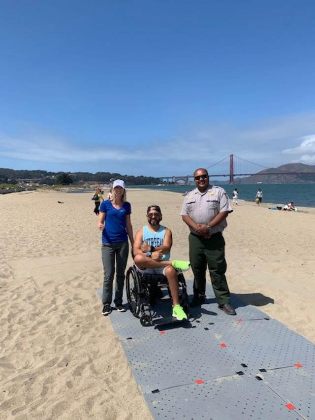 Kelly and National Park Accessibility Coordinator Richard stand next to adaptive athlete Aleco on the grey Beach Trax pathway at the beach overlooking the Golden Gate Bridge.