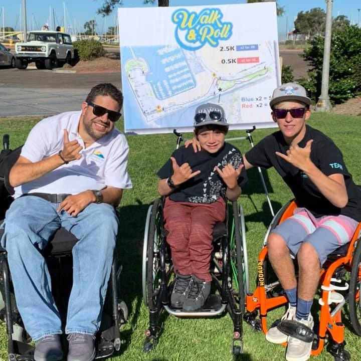 Beto Gurmilan, Hunter Pochop, and Parker Olenick smile in front of the Walk & Roll map on the grass at the event.