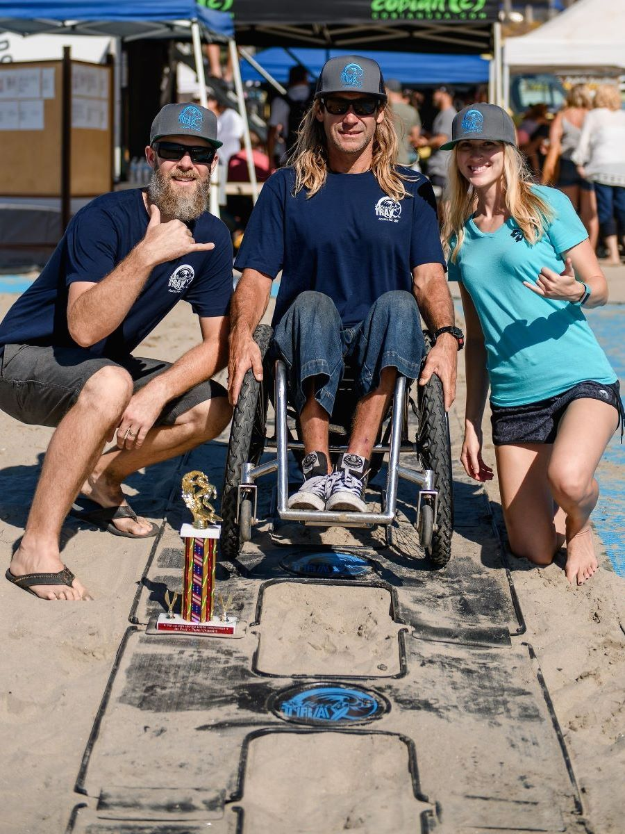 "Eric and Kelly pose with adaptive surfer Bruno Hansen while using the black plastic ""H"" shape Beach Trax panels on the sand."