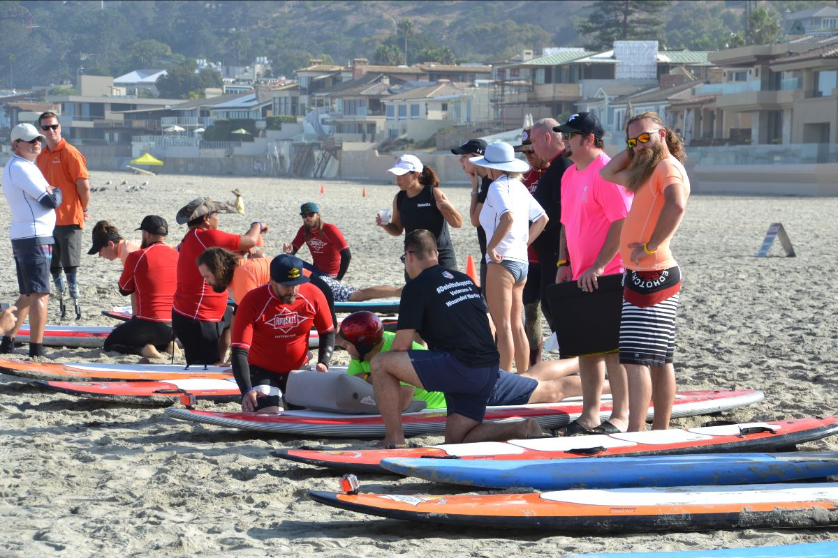 Surf instructors work with a veteran adaptive surfer on the beach to show him how to surf prone (on his belly).