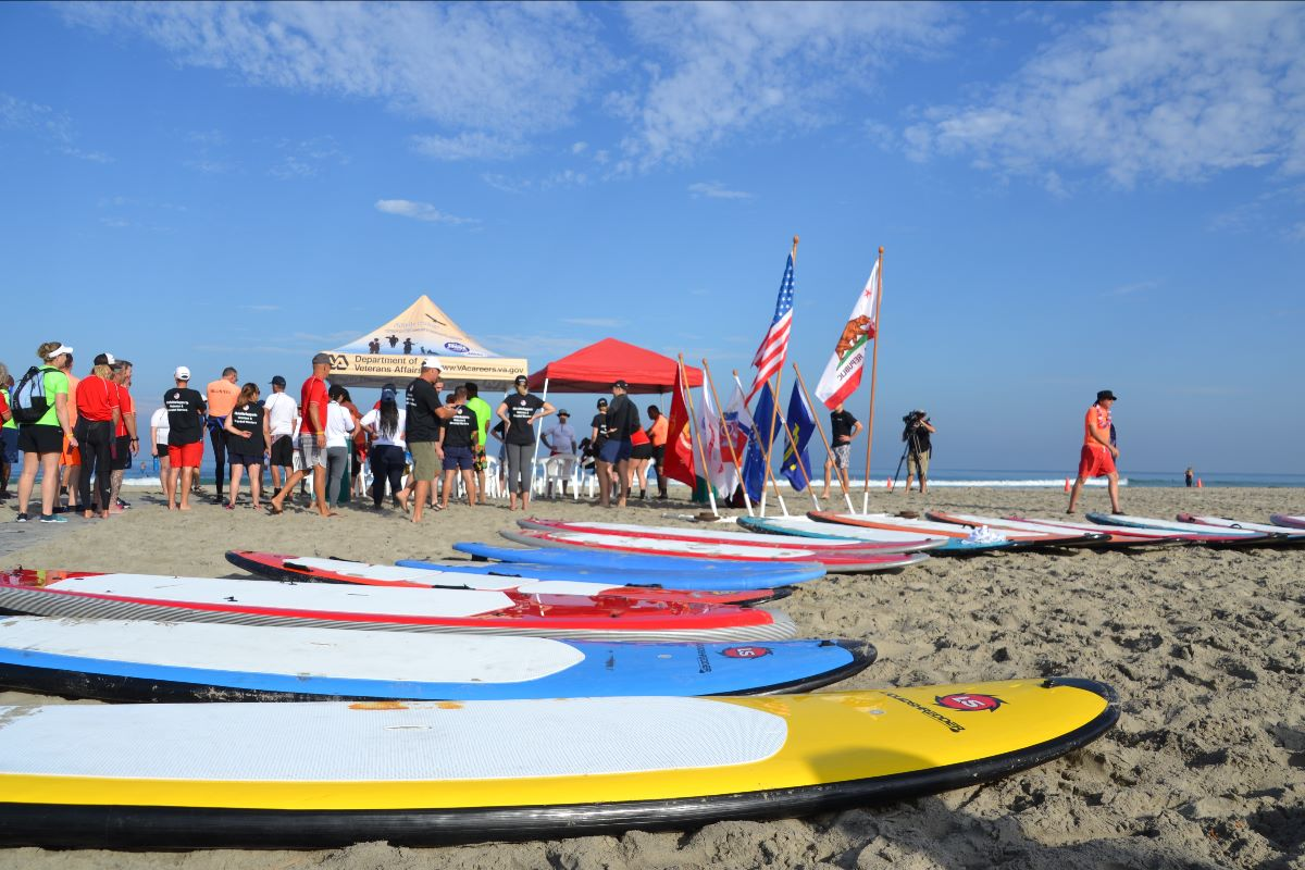 Colorful surfboards on the sand at the beach wit people and military flags in the background.