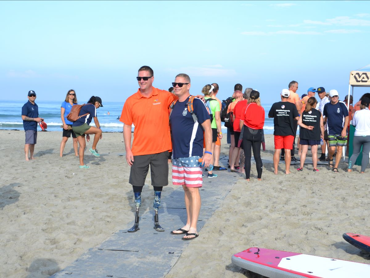 A man wearing an orange shirt with two prosthetic legs poses with a man wearing a blue shirt on a grey beach pathway at the event.