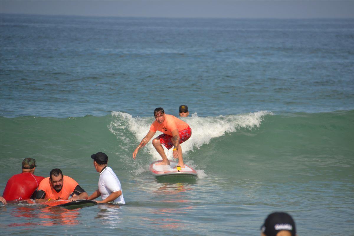 A man wearing an orange rash guard surfs a wave.