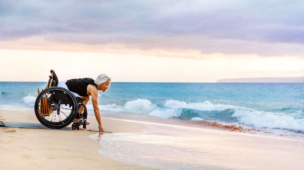 A woman using a wheelchair on the Beach Trax pathway leans down to touch the water at the beach during sunset with soft colors of blue, pink, and orange.