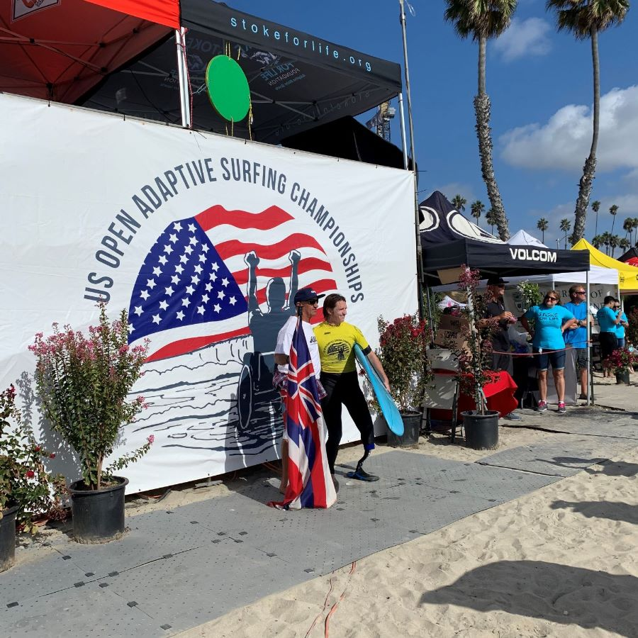 An adaptive surfer with left prosthetic leg wearing a yellow surf jersey and a man holding the Hawaii flag pose in front of the event banner on the beach.