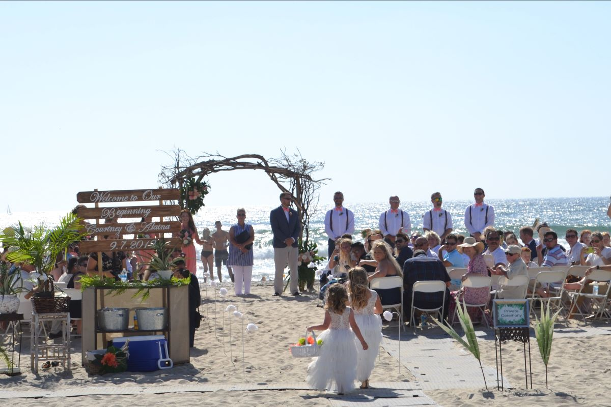 A beach wedding ceremony with guests watching the flower girls walk down the aisle.