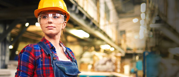 Woman in hard hat staring off into the distance, standing inside a factory.