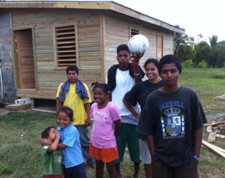 Some of Marynella's children outside the new addition to their home in the Valley of Peace.