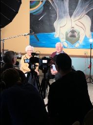 Two leaders from L'Arche Erie being recorded by videographers.