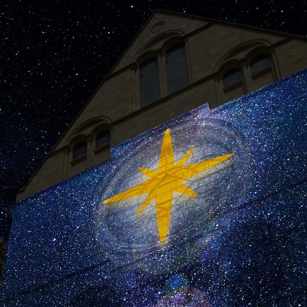Canterbury Cathedral with a giant star projected onto its side.